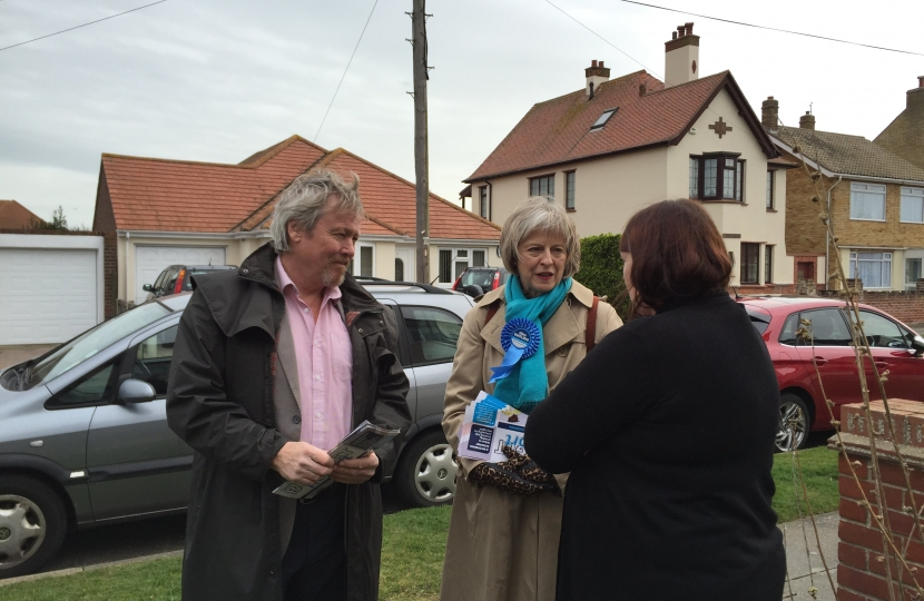 Giles Watling and Theresa May speak with a resident